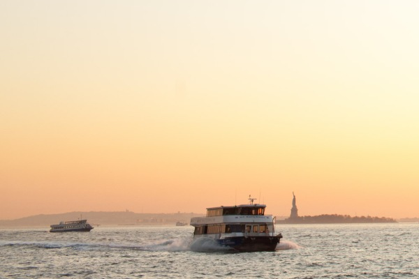 New York CIty River Taxi and the Statue of liberty at sunset
